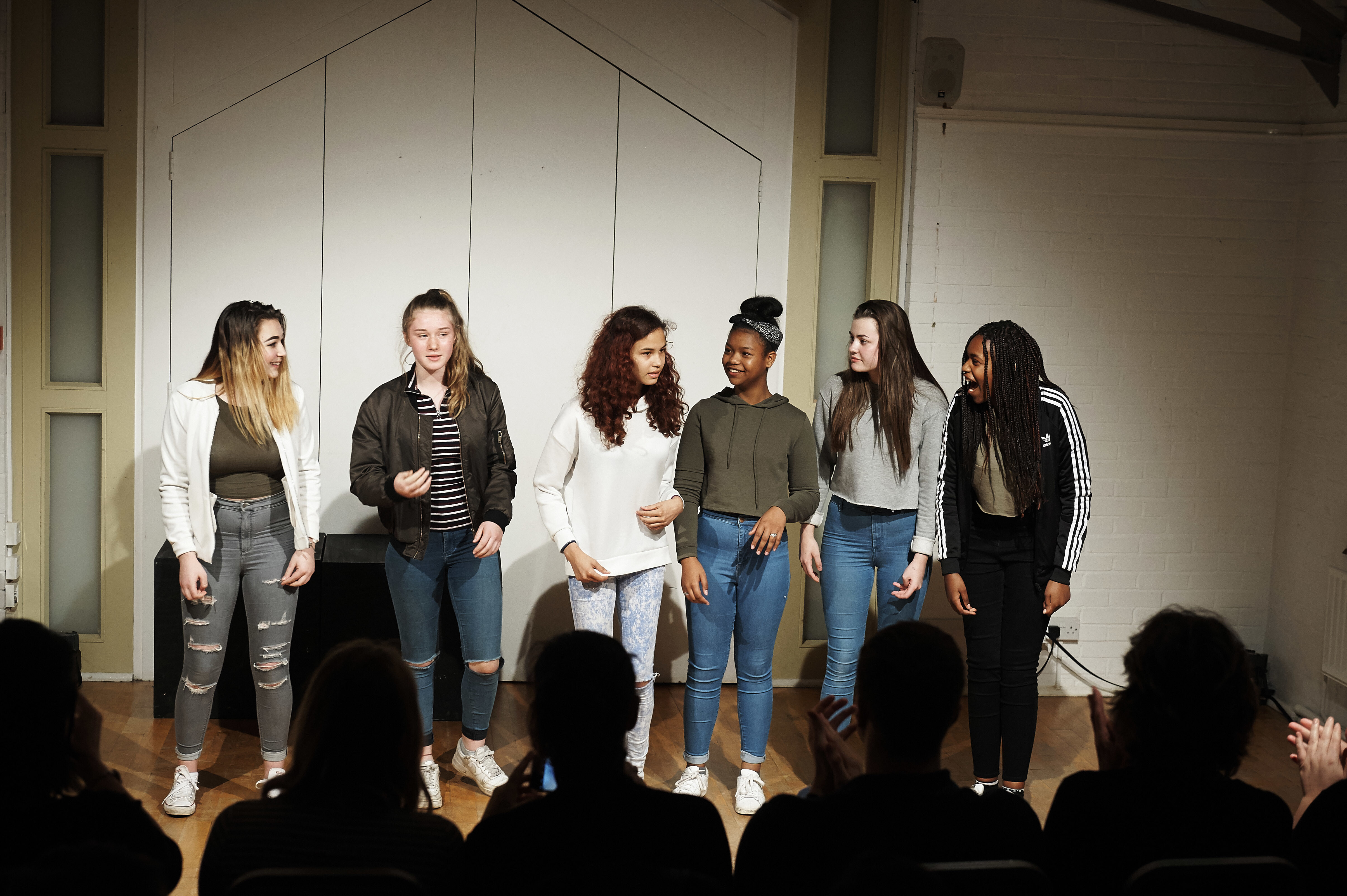 A group of teenagers performing a Play