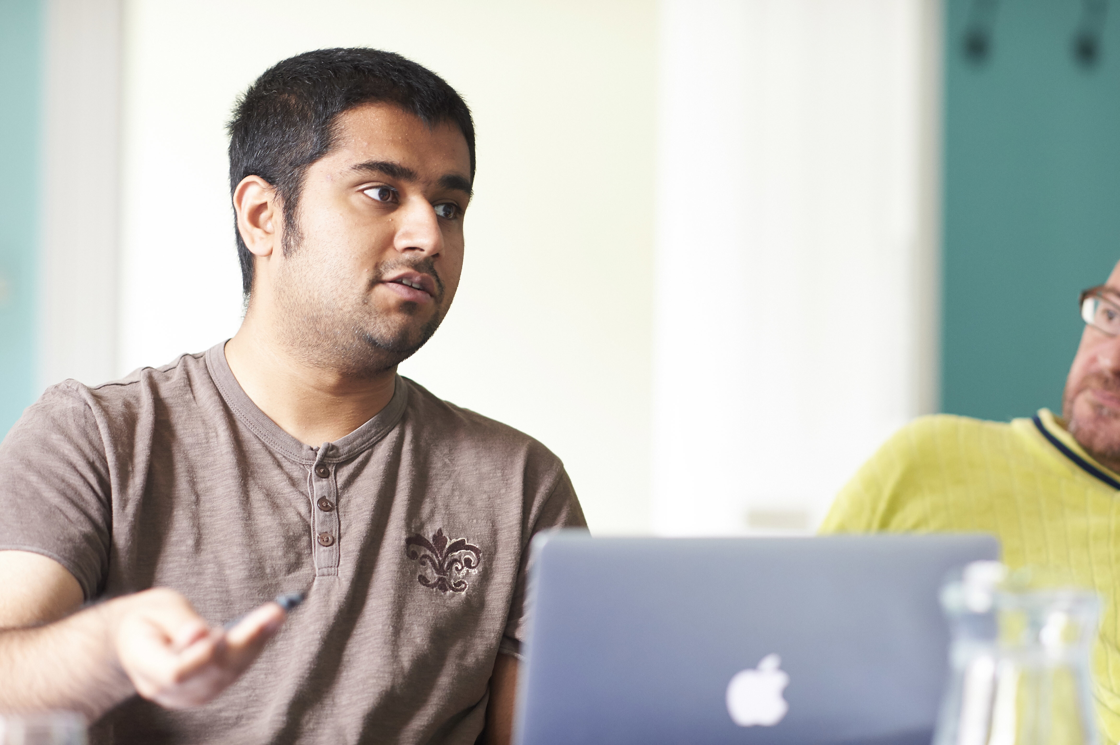 A member of a workshop discussing a project with a MAC laptop