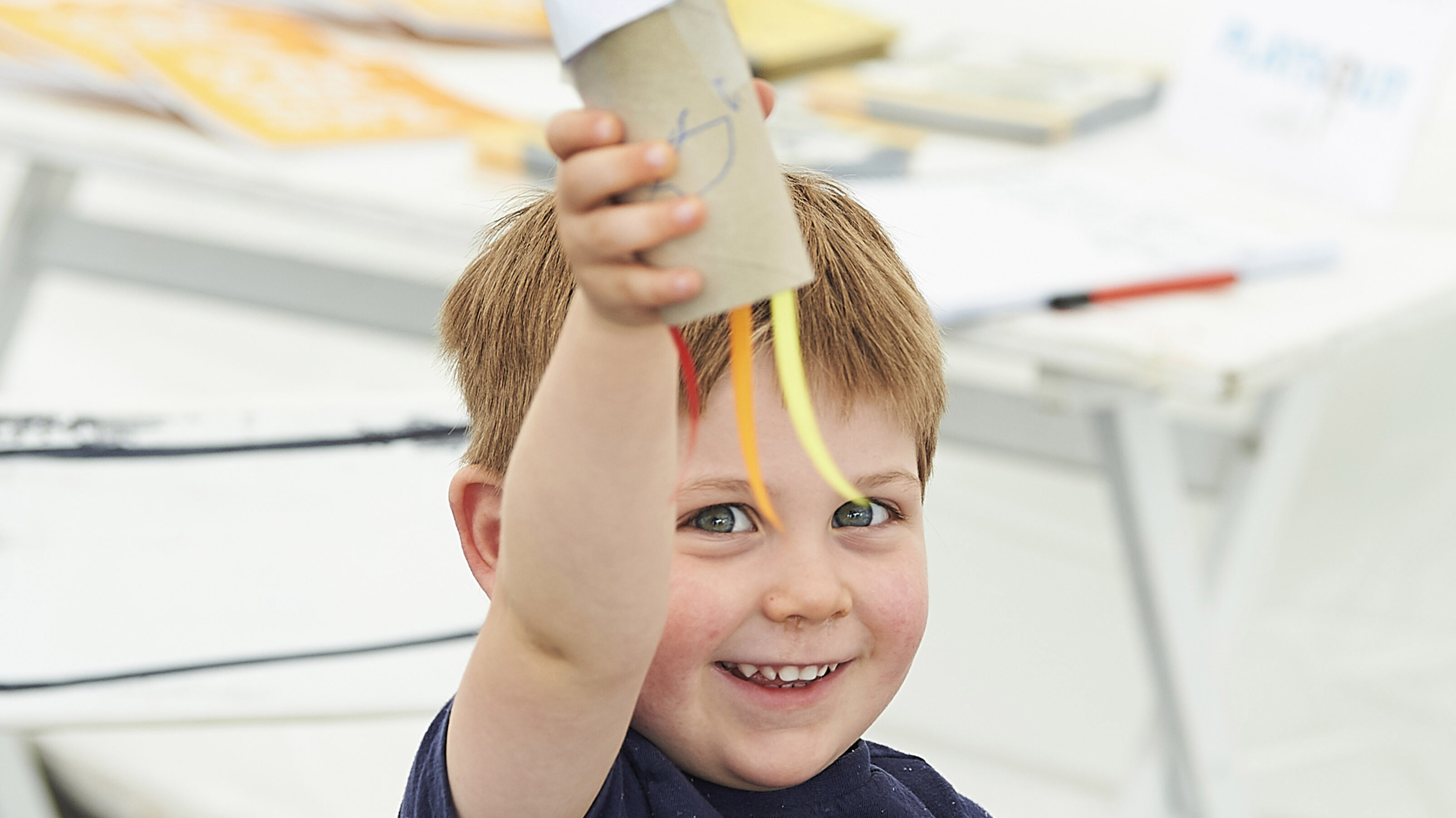 A toddler holding a puppet creation of a Rocket