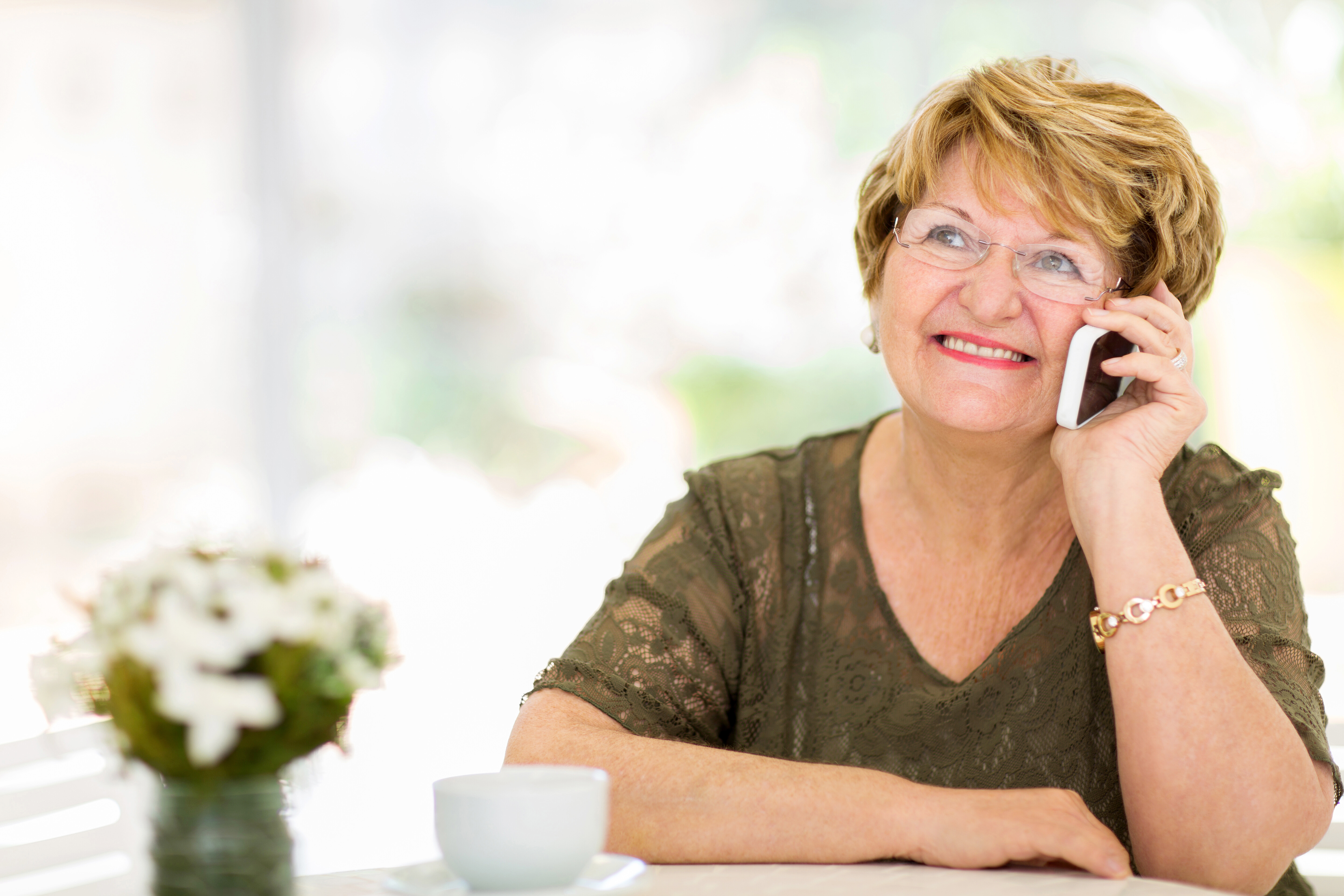 A closeup of a lady on a phone call with a cup of tea.