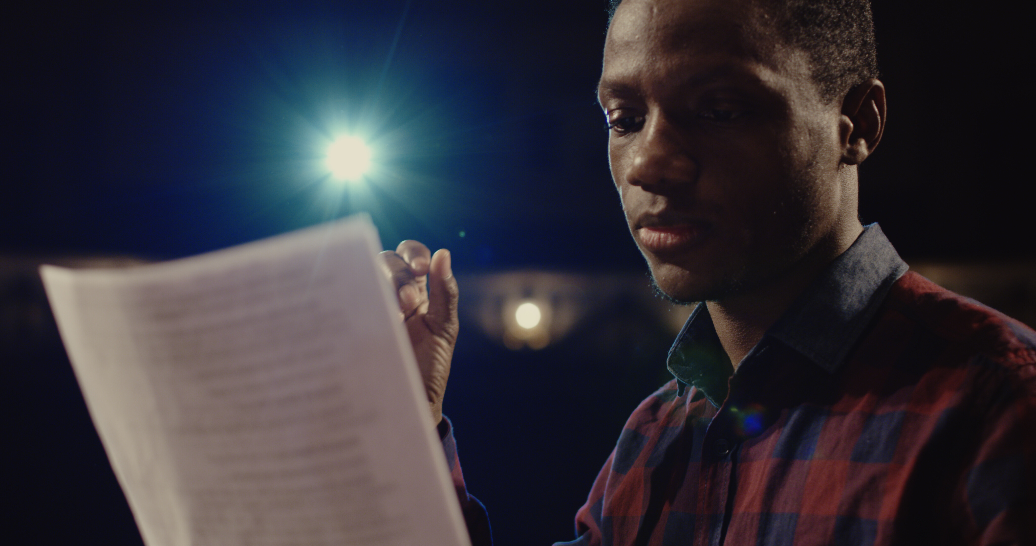 A man reading a script on a stage. A spotlight is shining on him.